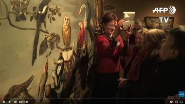 Personnes devant un tableau dans un musée