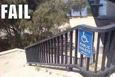 Panneau Public Toilets avec pictogramme de fauteuil roulant et flèche pointant vers un escalier à descendre