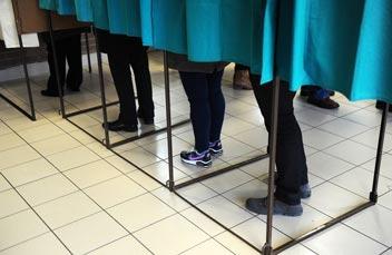 Photos de pieds dépassant par le bas de rideaux d'isoloirs de vote