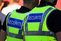 Dos d'hommes portant des gilets marqués du mot sécurité